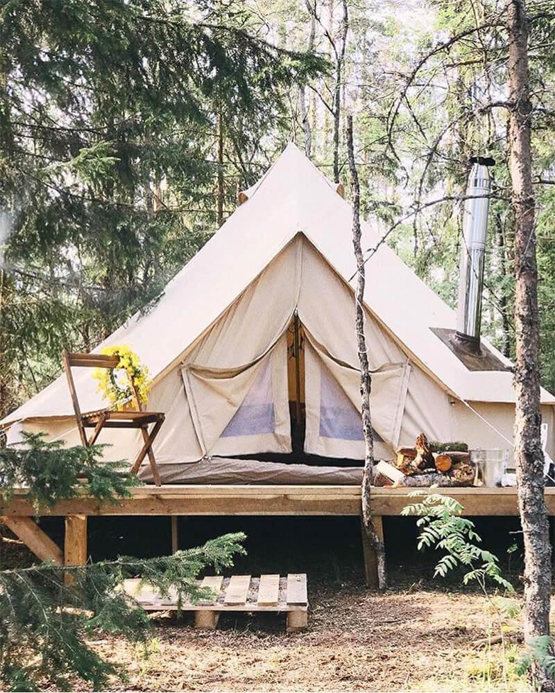 tente coton sibley sur terrasse en bois et poêle à bois